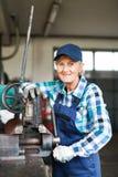 Senior female mechanic repairing a car in a garage. Stock Photos