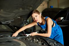 Female mechanic repairs the car with a wrench. Beautiful female mechanic repairs the car with a wrench Stock Photo