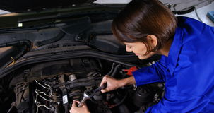 Female mechanic servicing a car stock footage