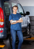 Female Mechanic Standing Arms Crossed By Car. Portrait of confident female mechanic standing arms crossed by car at garage stock photo