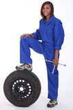 Female mechanic. Stood with a spare wheel Stock Image