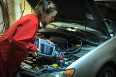 Female mechanic topping up the oil in a car Royalty Free Stock Images