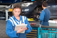 Female mechanic. Two mechanics at work in a garage. A woman in front checks off a maintenance sheet for periodic examination or mot test, with a man in the Stock Photos