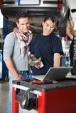 Female mechanic using laptop with client Royalty Free Stock Images