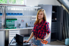 Female mechanic at work. auto service station. checked shirt Stock Photos