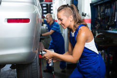 Female mechanic working on car tyre service Stock Photography