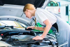 Female mechanic working in car workshop Royalty Free Stock Photo