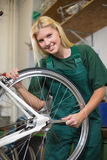 Female mechanic in workshop repairing a bicycle wheel Royalty Free Stock Photos