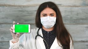 Female medic in white coat and protective mask holding in hand smartphone stock footage