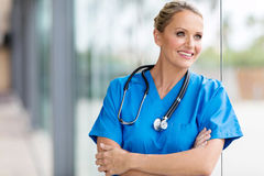 Female medical doctor. Beautiful female medical doctor looking outside window Stock Image