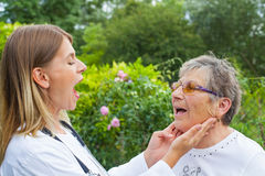 Doctor examining sore throat. Female medical doctor examining elderly women with sore throat in the garden stock image