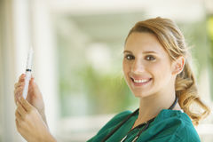 Female medical doctor. Happy female medical doctor with syringe Royalty Free Stock Photography