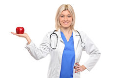 Female medical doctor holding a red apple Stock Photo