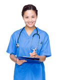 Female medical doctor write on clipboard Royalty Free Stock Photo