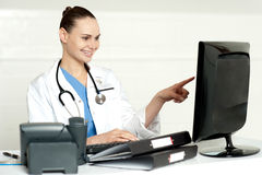 Female medical expert pointing at computer screen Stock Image