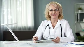 Female medical expert with tablet in hands smiling in camera, sitting cabinet stock photo