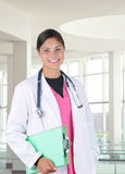 Female Medical Professional. Young female medical professional wearing scrubs and a lab coat in modern medical facility. Person is smiling and holding a clip Stock Images