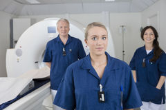 Female Medical Professional With Colleagues Standing By MRI Mach Royalty Free Stock Image