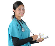 Female medical professional with Medicine. Smiling female medical professional in scrubs Holding clip board and prescription bottles. Square format isolated on Royalty Free Stock Photography