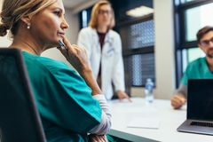 Female medical professional in staff meeting stock photography