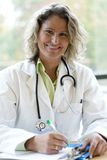 Female medical professional writing. Female medical professional indoors writing royalty free stock photo