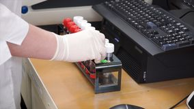 Female medical or scientific researcher using test tubes on laboratory. Clip. Female Scientist Analyzes Liquid in the stock photo