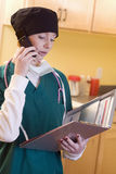 Female medical staff with records. Medical professional wearing surgical gear holding medical chart and talking on cell phone Stock Photography