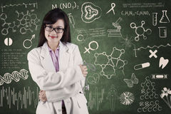 Female medical student at class. Beautiful female doctor smiling in front of medical background Royalty Free Stock Photo