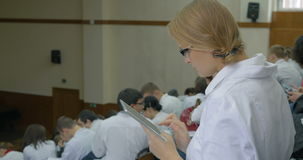 Female medical student with pad on the lecture. Female medical student using tablet computer on the lecture at the university or at the conference, then she stock video footage