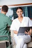 Female Medical Technician Holding Clipboard Stock Photo