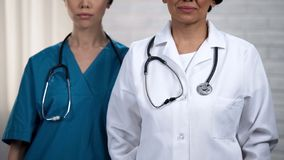Female medical workers confidently looking at camera, high quality of treatment. Stock photo stock photos