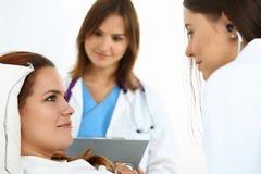 Female medicine doctor communicating, examining and listening wi Stock Photos