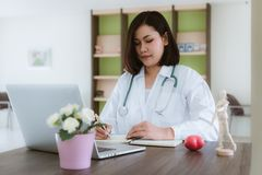 Female medicine doctor examining and writing health report of patient in her office., Professional medical stethoscope instrument royalty free stock photos