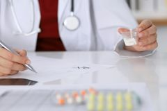 Female medicine doctor fills up  prescription form to patient closeup. Panacea and life save, prescribe treatment, lega. Female medicine doctor fills up Stock Photos
