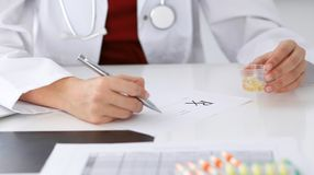 Female medicine doctor fills up  prescription form to patient closeup. Panacea and life save, prescribe treatment, lega. Female medicine doctor fills up Royalty Free Stock Photo