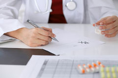 Female medicine doctor fills up  prescription form to patient closeup. Panacea and life save, prescribe treatment, lega. Female medicine doctor fills up Royalty Free Stock Photography