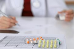 Female medicine doctor fills up  prescription form to patient closeup. Panacea and life save, prescribe treatment, lega. Female medicine doctor fills up Stock Photo