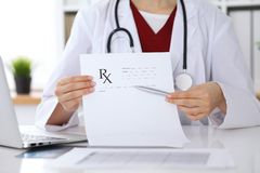 Female medicine doctor hand hold clipboard pad and give prescription to patient closeup. Panacea and life save Stock Photos
