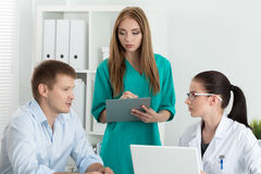 Female medicine doctor with her colleague consulting patient. Female medicine doctor with her colleague consulting male patient. Healthcare and medicine concept Stock Photography