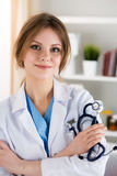 Female medicine doctor at her office. Female medicine therapeutist doctor standing with hands crossed on her chest holding stethoscope in office. Medical help or Royalty Free Stock Photo