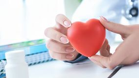 Female medicine doctor hold in hands red toy heart close -up. Cardio therapist student education concept. Female medicine doctor hands holding red toy heart royalty free stock photography