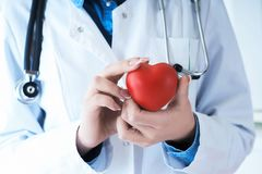 Female medicine doctor hold in hands red toy heart close -up. Cardio therapist student education concept. Female medicine doctor hands holding red toy heart royalty free stock image
