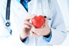 Female medicine doctor hold in hands red toy heart close -up. Cardio therapist student education concept. Female medicine doctor hands holding red toy heart royalty free stock images