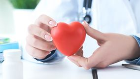 Female medicine doctor hold in hands red toy heart close -up. Cardio therapist student education concept. Female medicine doctor hands holding red toy heart stock photos