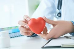 Female medicine doctor hold in hands red toy heart close -up. Cardio therapist student education concept stock photography