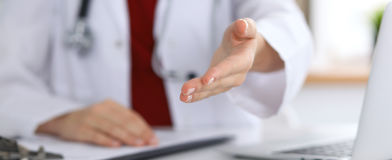 Female medicine doctor offering helping hand in office closeup. Physician ready to examine and save patient. Friendly. And cheerful gesture. Medical cure and Royalty Free Stock Images
