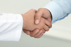 Female medicine doctor shaking hands with male patient. Partnership, trust and medical ethics concept. Handshake with satisfied client. Healthcare and medical stock photography