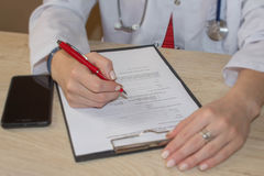 Female medicine doctors hands filling patient medical form. Phys Royalty Free Stock Image