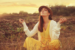 Female meditate sitting on a deadwood autumn field. Royalty Free Stock Photography