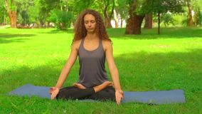 Caucasian woman sitting in lotus position. Female meditates on the blue mat in park girl with long curly hair doing yoga. nature landscape with green grass and stock footage